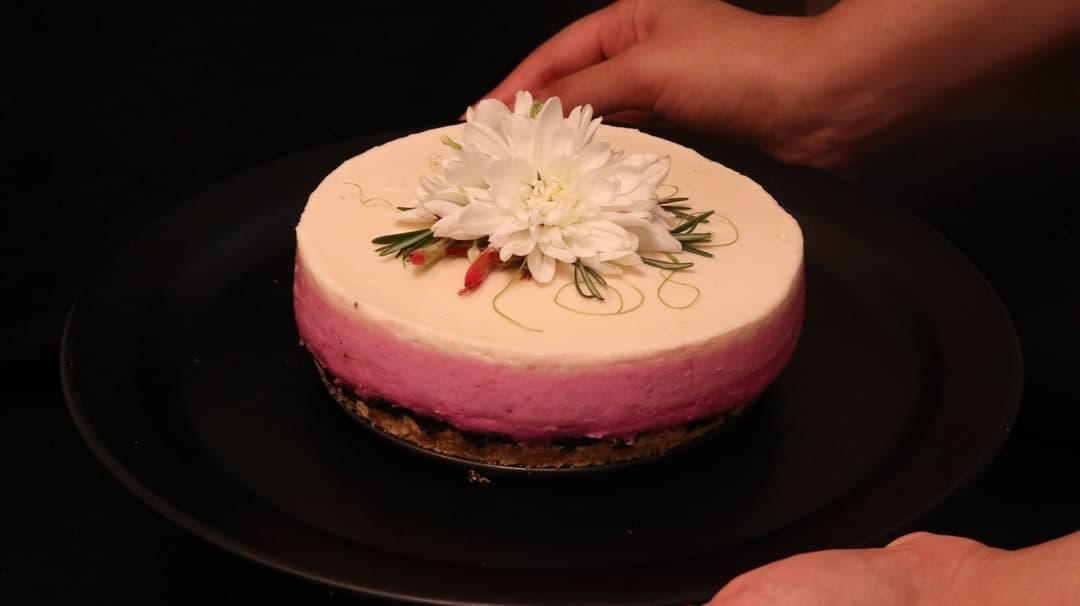 A person sitting at a table with a cake on a plate