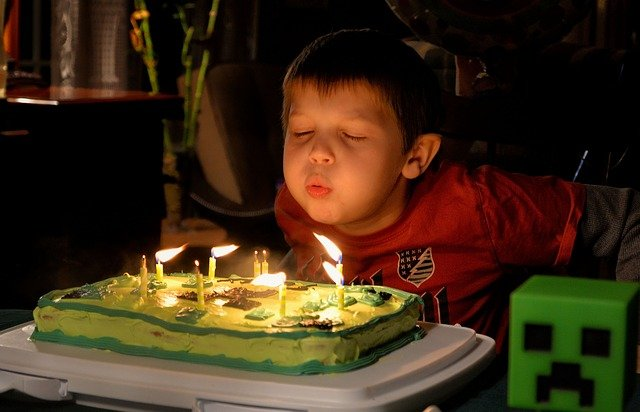 A little boy sitting at a table in front of a birthday cake